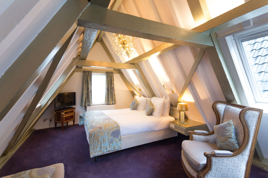 Hotel room with two floors showing the top floor with purple theme and a view on the Amsterdam Canal Belt rooftops