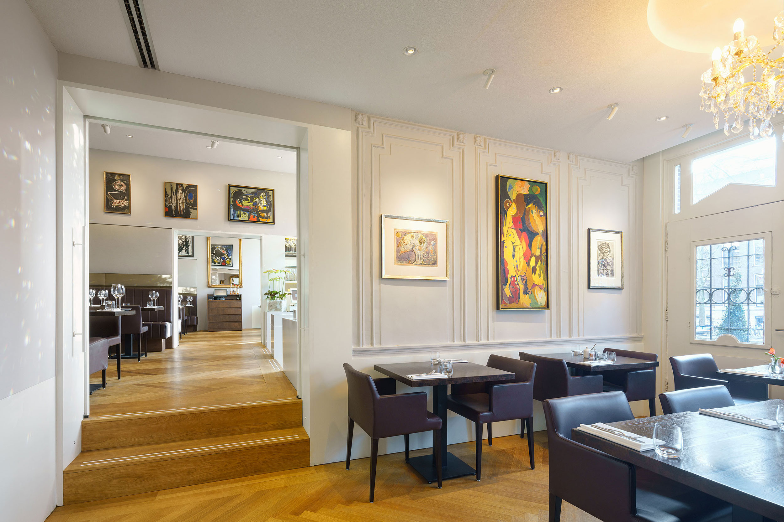 Brasserie Ambassade as seen from the Private Dining, with paintings by cobra artists adorning the walls and a view on Herengracht