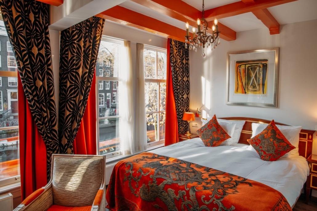 Kamer met oranje tinten en met uitzicht op Herengracht in Ambassade Hotel Amsterdam